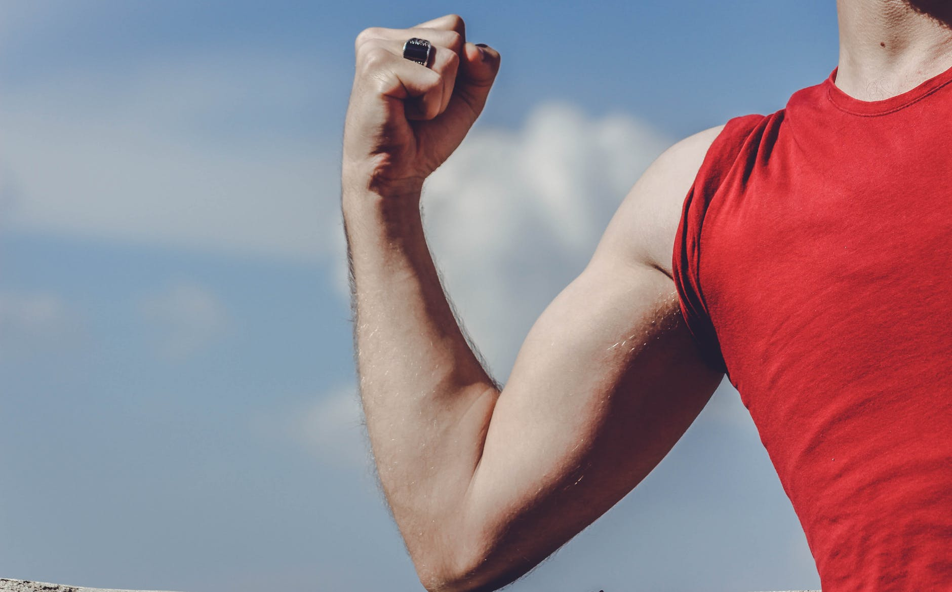 man raising his right arm
